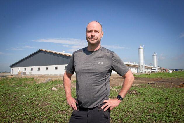 Grisproducenten Mattias Espert framför det nya grisstallet som invigs i dagarna.
