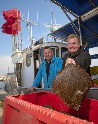 André och pappa Joakim visar upp dagens fångsten av piggvar.