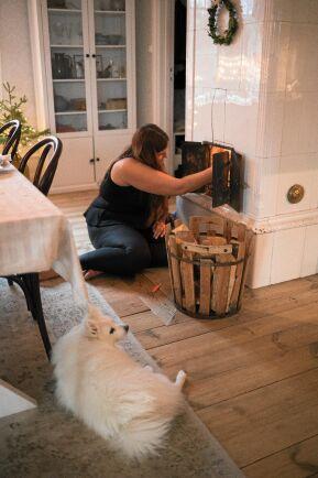 Karin eldar i den gamla kakelugnen i vardagsrummet som har originalgolv från 1891.