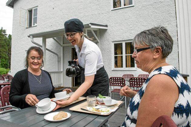 Asta serverar kaffe till gästerna Berit Norén och Anki Södermark från Skellefteå på uteserveringen.
