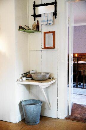 Enkelt och omodern standard med handfat och hink i köket.