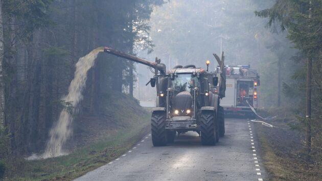 Hästveda tidigare i våras: Med hjälp av traktor och gödseltank vattenbegjuter en av traktens lantbrukare vägarna för att hindra skogsbrandens framfart.