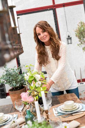 Susann ser till att lägga en sista hand vid blomsterarrangemanget. Hon använder gärna fynd från trädgården. Foto: Pia Gyllin