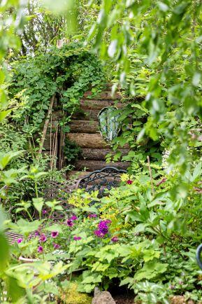 Sagolik och ombonad. Sådan är stämningen i Monicas frodiga trädgård.