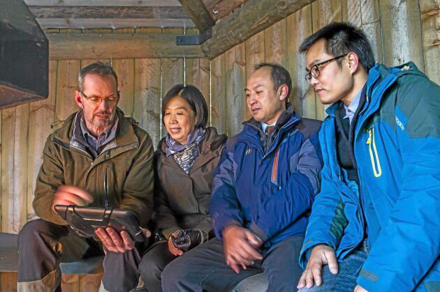 """Norramedlemmen och skogsägaren Svarte Swartling i Norrfors utanför Umeå berättar om sitt skogsbruk och skogsbruksplanen i """"paddan"""" för Wang Dong, skogsforskare, Hu Yuanhui, biträdande generaldirektör för Kinas skogsminsterium och Xie Heshen från CAF i Kina. Vindskyddet med värmande brasa uppskattades efter en skogspromenad i minusgrader."""