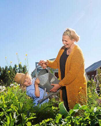 Trädgårdskul. 4-årige Calle vill vara med mamma Maria när hon vattnar i trädgårdslanden.