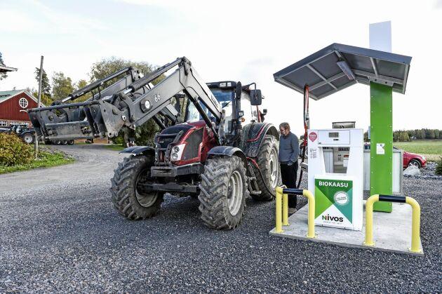 """Markus Eerola fyller den hyrda traktorn av märket Valtra med gården egen biogas. Traktorn är en testmodell """"Dual Fuel """"som klarar att köra på både biogas och dieselbränsle."""