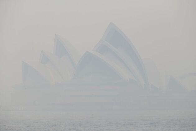 Tjock rök från skogsbränderna skymmer Sidneys välkända operahus på tisdagen. Myndigheter uppmanar befolkningen att stanna inne.