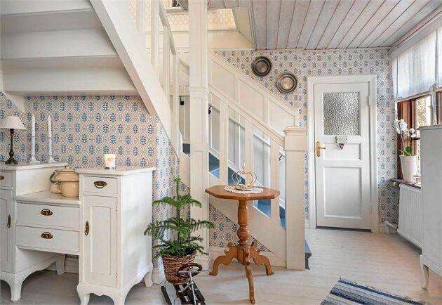 En vitmålad trapp leder upp till övervåningen.