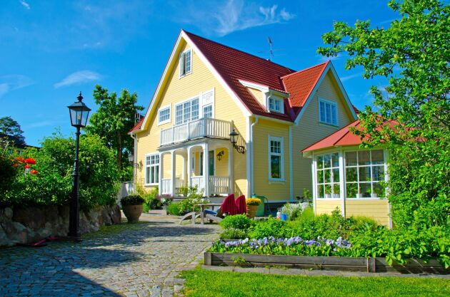 Ett hus målat med ljusgul och vit linoljefärg. Soligt utan irriterande blänk.