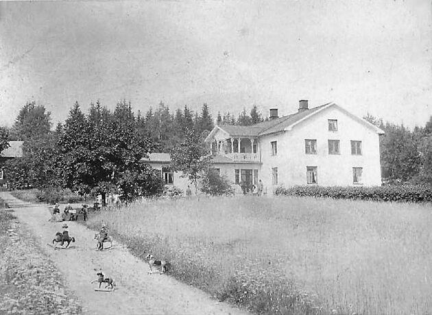 Sommaridyll 1895, med barn på varsin gunghäst på grusvägen och tre damer i hatt i varsin vilstol.