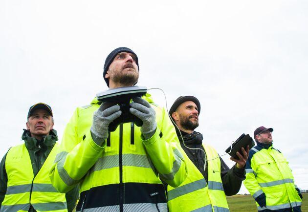 Koncentration. Vinden är besvärlig när Petter Ellgård går in för landning med drönaren. I bakgrunden studiekamraterna Mats Johansson, till vänster, och Daniel Levall, till höger. Utbildningsledaren Nicolas Tegsell håller koll i ipaden.