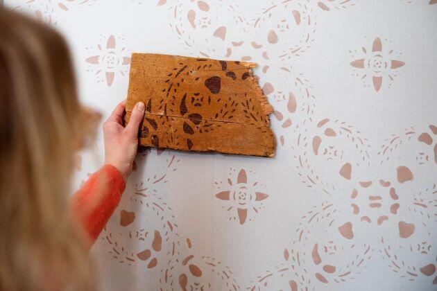 Jenny med en bit av den schablonmålade vägg vars mönster hon använde som förlaga.
