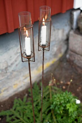 Vackra ljushållare av glas i hållare av fint rostig järn sprider ljus utomhus.