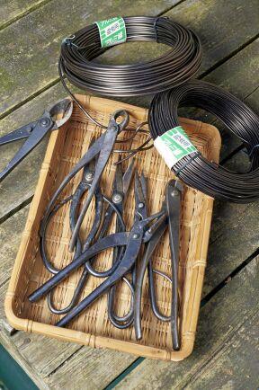 En bonsaiodlares specialverktyg. Här finns olika avbitartänger och andra redskap för att klippa och beskära rötter och grenar och bruneloxerad aluminiumtråd för att linda grenarna.
