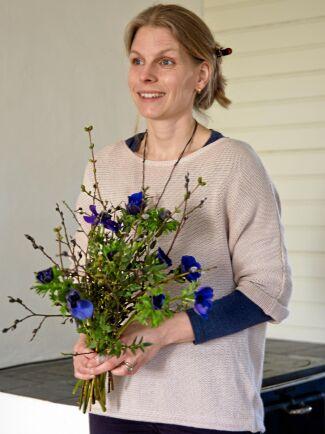 Maria Zaar med kvistar med nyutslagna löv och knoppar och mörkblå anemoner. Hon är inte mycket för prydnadssaker utan gillar att inreda med saker från naturen blandat med lite arvegods eller kära minnessaker.