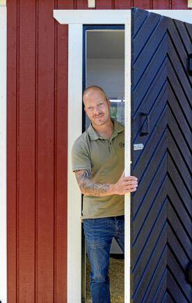 Patric Dalfjärd kikar ut ur det fiffiga hönshuset i familjens trädgård.