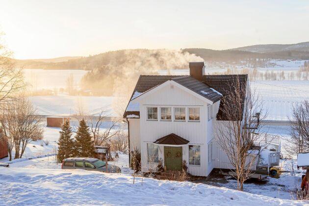 Från det vita trähuset ser man ut över sjön och skogsklädda berg.