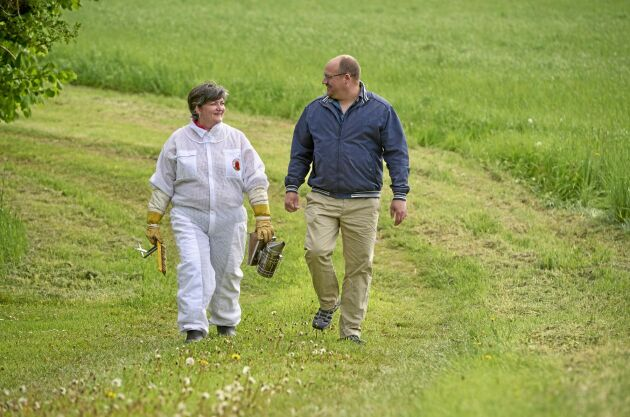 Monica och Lars Larsson på väg till bikuporna ute på fältet hos Honungsgården på Bjäre i Skåne.