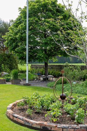 En vältrimmad gräsmatta håller ihop och lugnar ner i en trädgård med många olika växter, sittplatser och avdelningar.