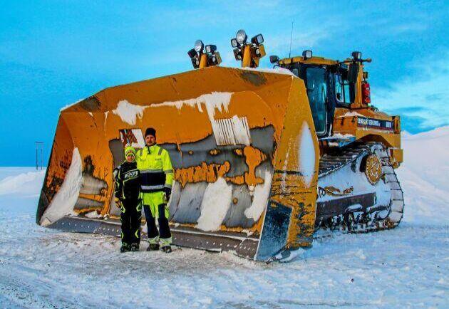 Magnus Ljungberg och sonen Alexander Ljungberg spakar D8:an med det gigantiska snöbladet.