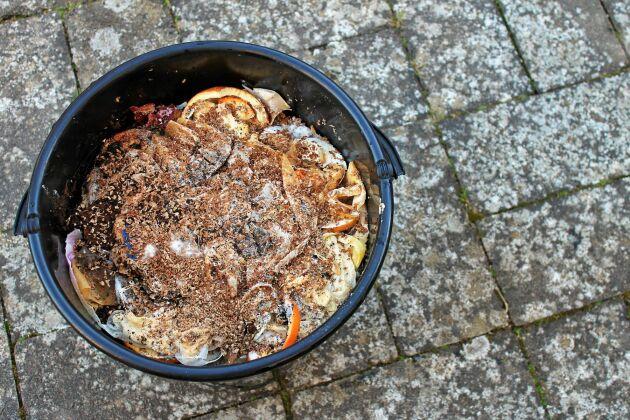 Matskräp varvat med strö i hinken.