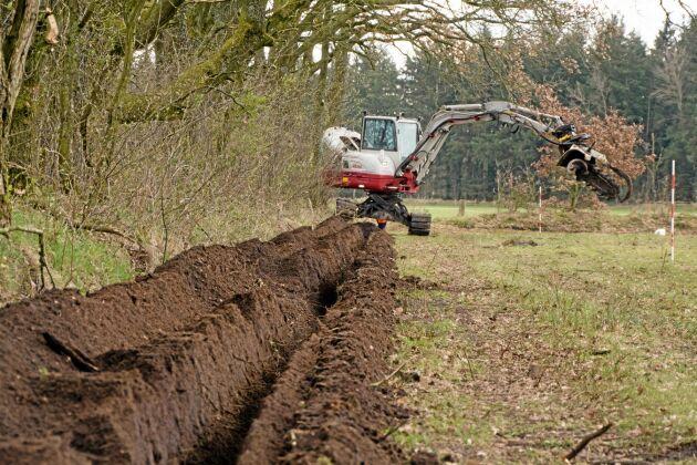 Grävskopan banar väg för staketbygget genom att göra ett fyra decimeter brett dike där stolparna sedan placeras.
