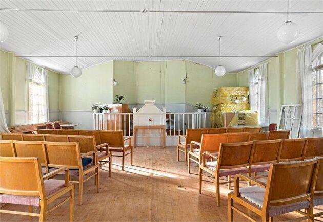 I kyrksalen står stolsrader och altare kvar. Fönstren har vackra detaljer.