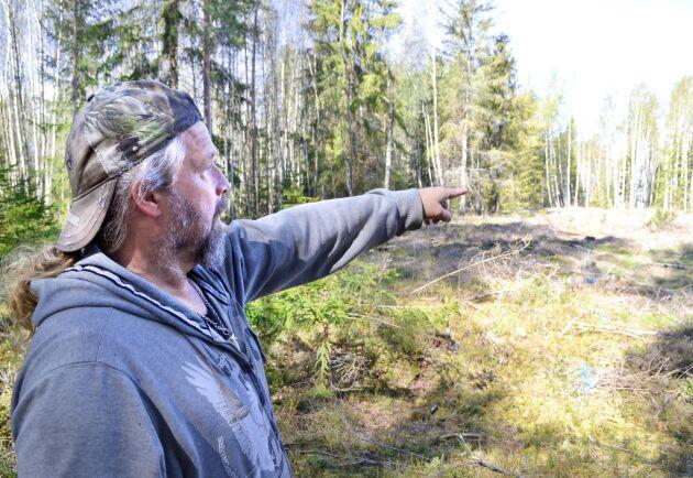 Marcus Werjefeldt pekar ut var gränsen går enligt GPS-en. Det innebär att hyggeskanten i bakgrunden ligger uppåt 10 meter in på hans mark.