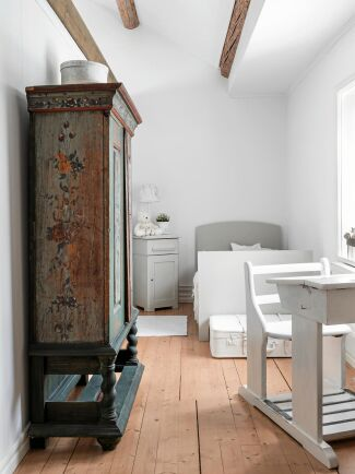Edyta och Marcus gemensamma dotter Tindra, 7 år, har rummet intill deras sovrum. Sängen är en växasäng, fyndad på loppis och har målats grå. Skåpet är i från 1800 talet och skolbänken ett auktionsfynd.