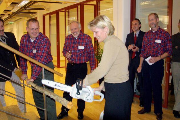 """Dåvarande """"skogsministern"""" Ulrica Messing invigde den nya skogstidningen genom att såga av en trädstam. I bakgrunden Skogslands redaktion i rutiga skjortor, Rolf Segerstedt, Torbjörn Wennebro och Sven-Olov Larsson, samt VD Patrik Widlund i kostym."""
