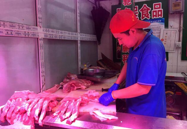 En kinesisk slaktare styckar fläskkött vid en marknad i Peking. Arkivbild.