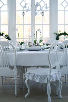 Blomsterarrangemang, julkulor i mossa och andra gröna växter bryter av det annars ljusa rummet.