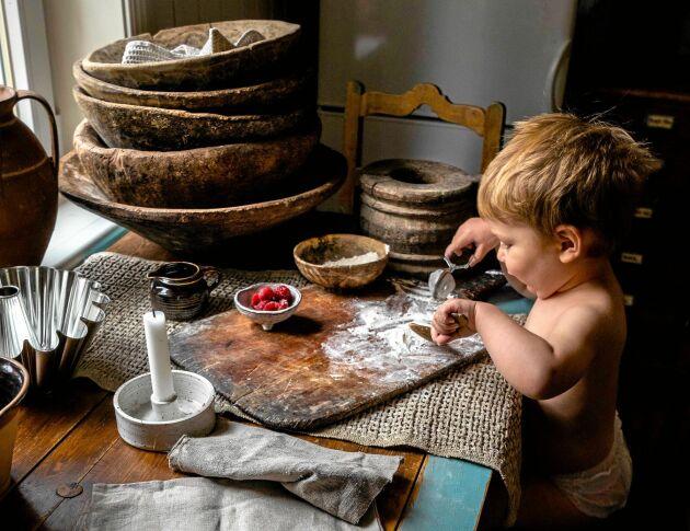 Sonen Valter bakar på den vackert slitna träskärbrädan. Intill står rejäla fat och skålar av trä.