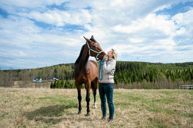 Njuter av livet på sin hästgård. Eva älskar att få vara med sina hästar hela dagarna och vara ute i den friska luften utomhus. Varmblodet Perry ger henne en kärvänlig puss.