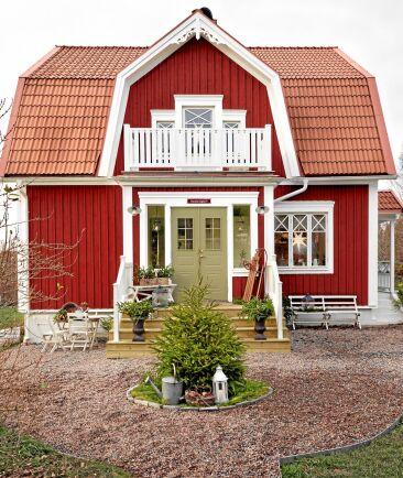Ett rött hus med vita knutar från 1921, som andas lantlig charm. På gårdsplanen möts gästerna av granris i olika arrangemang.