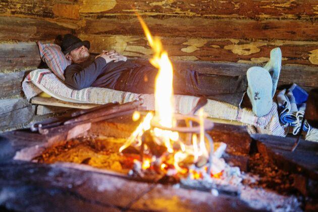 Owe tar en tupplur inne i fäbodens eldpallskoja där elden sprakar.