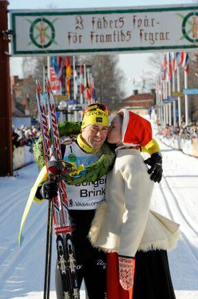 Jörgen Brink vinner sin tredje raka seger i Vasaloppet och får en segerkram av kranskullan Johanna Axelsson.