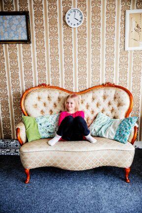 Felicia i gammelfarmors soffa som bevarats, med gammeldags tapet på väggen bakom.