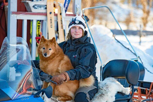 Jenny älskar sitt fria liv i den norrbottniska glesbygden. Här med hunden Eldar på skotern.