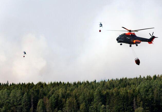 Arkivbild från Salabranden 2014 där helikoptrar brandbekämpar med vattenbombning.