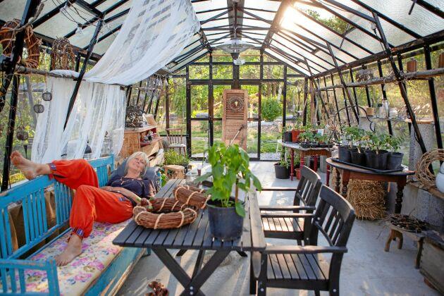 Susanne kopplar av i sitt vackra växthus, en av alla de sköna viloplatser hon har skapat.