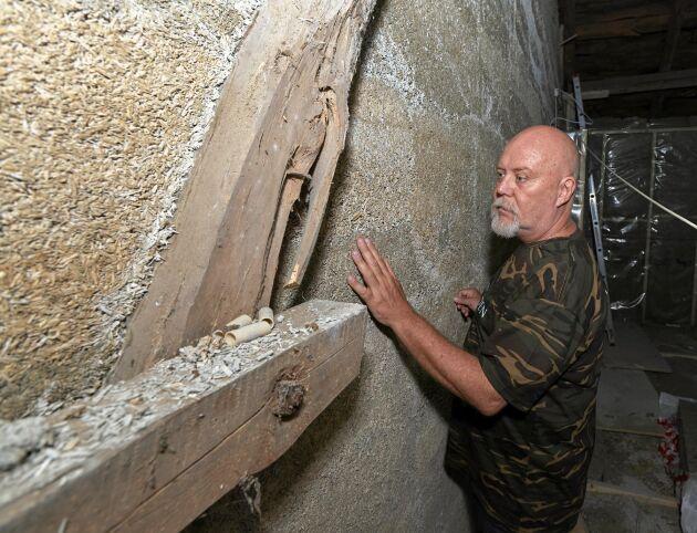 Robert känner på den lena väggen som isolerats med hampans långfiber.