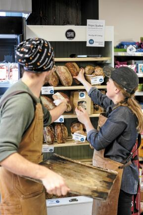 Paret fyller på nybakt bröd i bageriets eget skåp i Ica-butiken.
