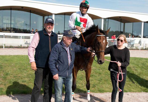 Binoche e. Bated Breath GB, här med jockeyn Elione Chaves och uppfödaren Ivan Sjöberg till vänster samt Jan Erik Pettersson och hästen skötare, efter seger på Bro Park.