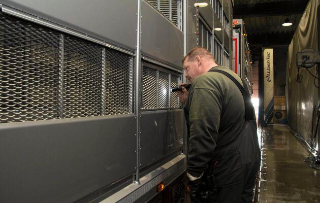 René Dixen, medarbetare på Mega Wash, kontrollerar statusen på en djurtransport med hjälp av ficklampa.