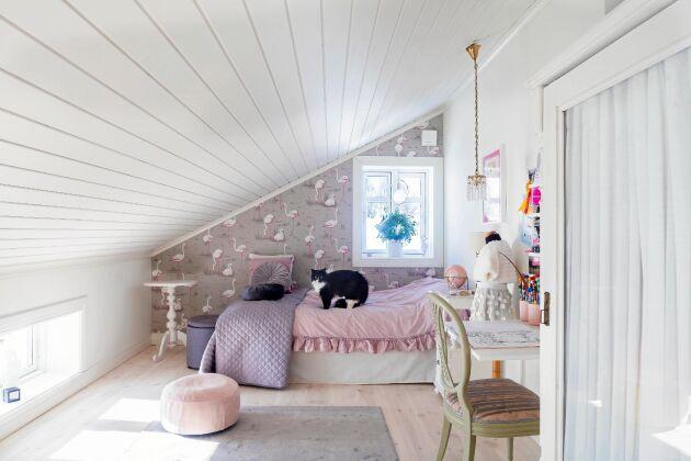 Dottern Idas vindsrum har snedtak och går i vitt, rosa och grått. På sängen vilar katten Kalle.