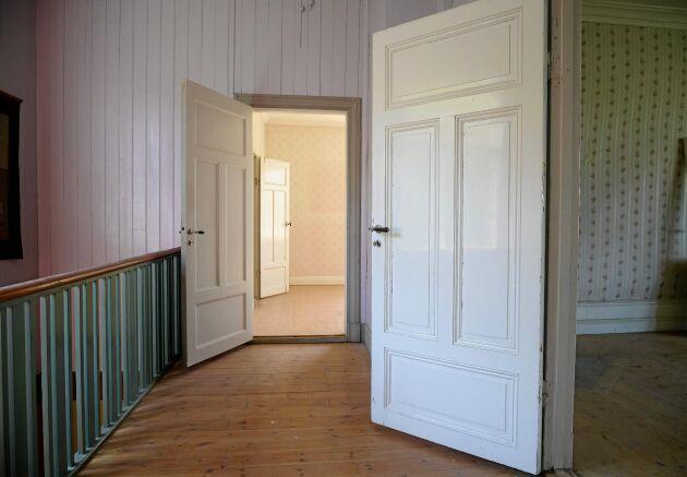 Bevarad interiör i hallen på andra våningen med spegeldörrar och panel.
