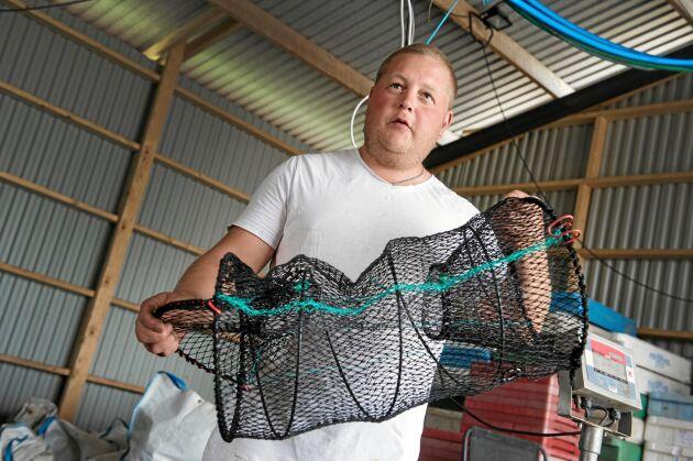 Jimmy med en av de 400 kräftburar som han och de andra fiskarna i släkten fångar 10-12 ton kräftor per år med.