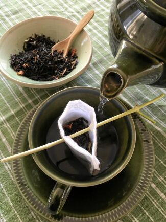 Tvätta och använd igen. Tepåsen av tyg hängs på en liten kvist.